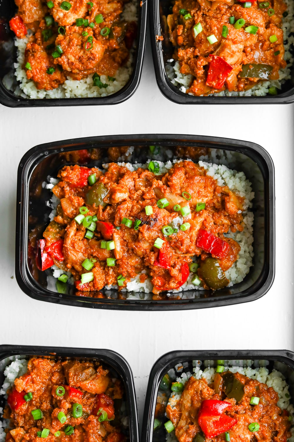 A meal prep container filled with cauliflower rice and topped with BBQ chicken and vegetables.