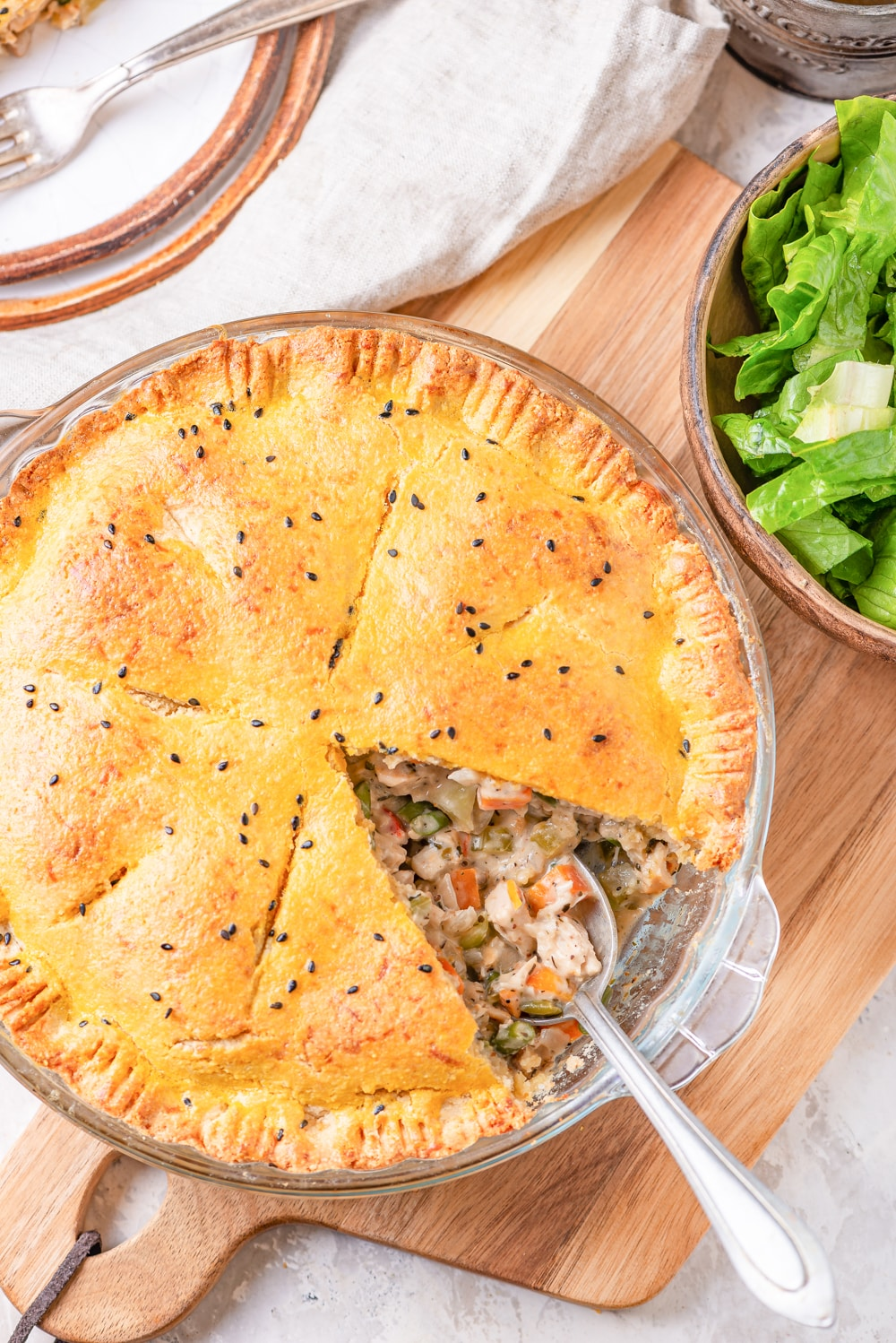 A pie plate board filled with chicken pot pie on top of a cutting and next to a bowl of lettuce.