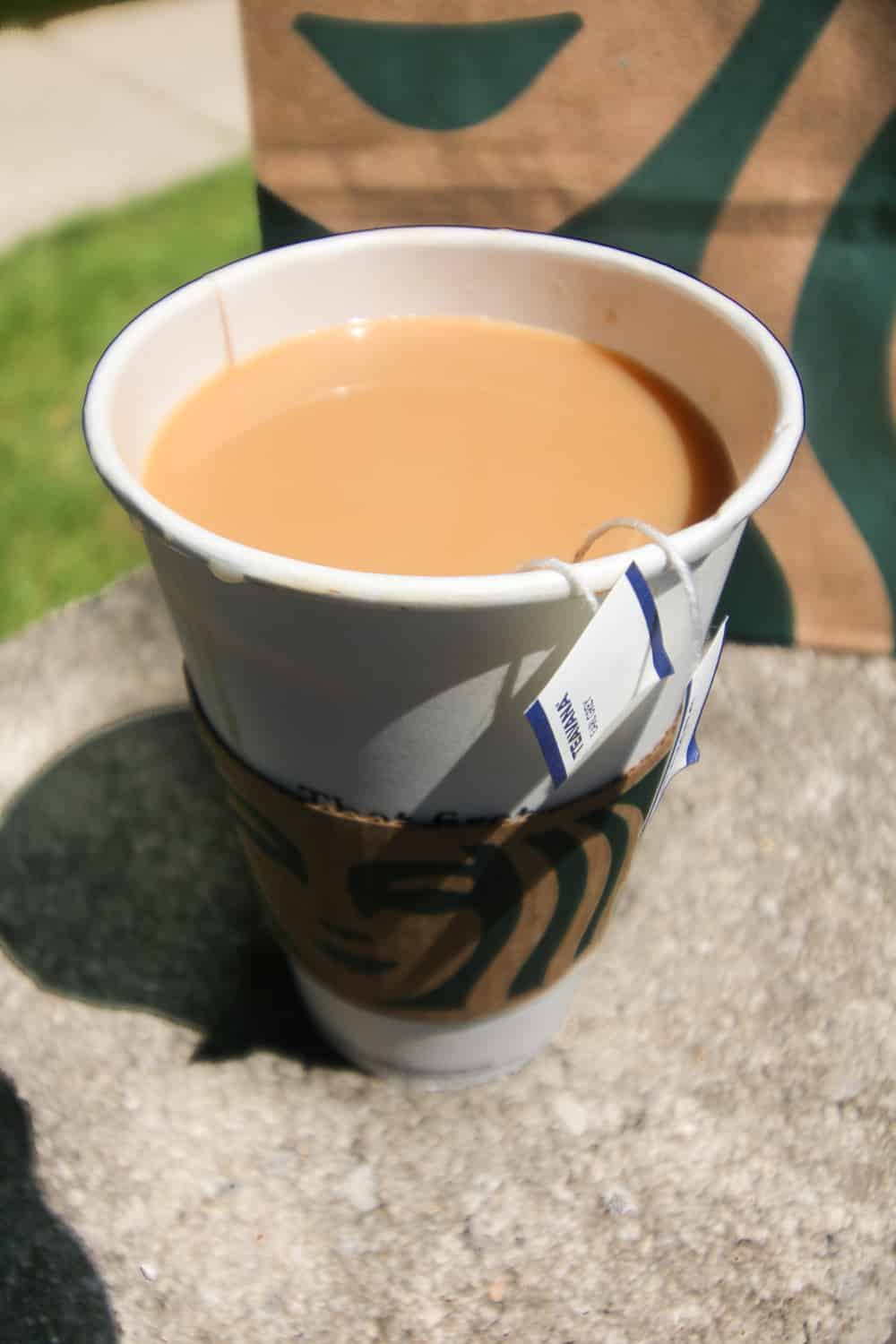 A large paper coffee cup filled with tea and cream.