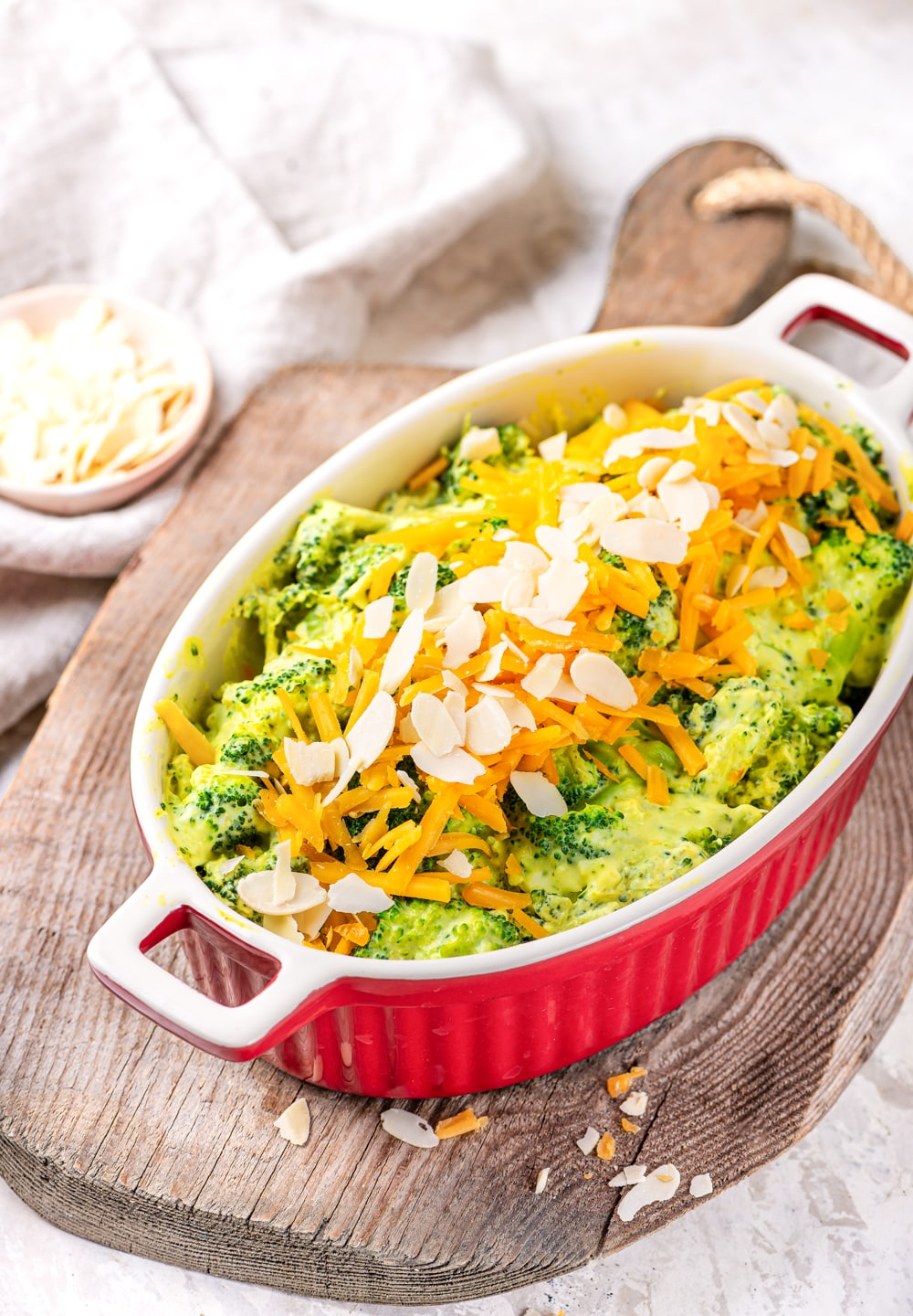 A casserole dish filled with broccoli covered in cheese sauce, and topped with shredded cheddar cheese and sliced almonds.