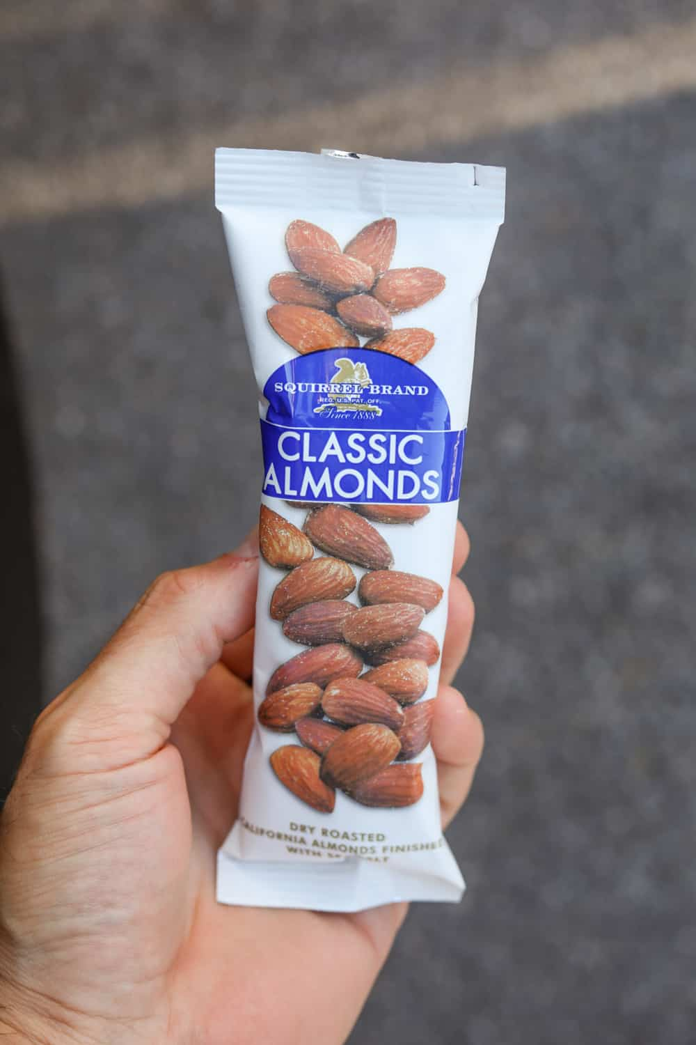 A hand holding a package of almonds.