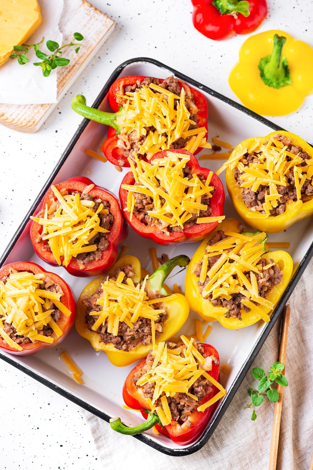 8 bell peppers halves stuffed with ground beef and topped with unmelted cheddar cheese on a baking sheet.