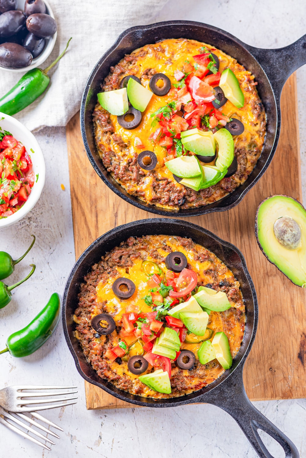 2 Cast iron skillets filled with ground beef, cheese, salsa, and pieces of avocado.
