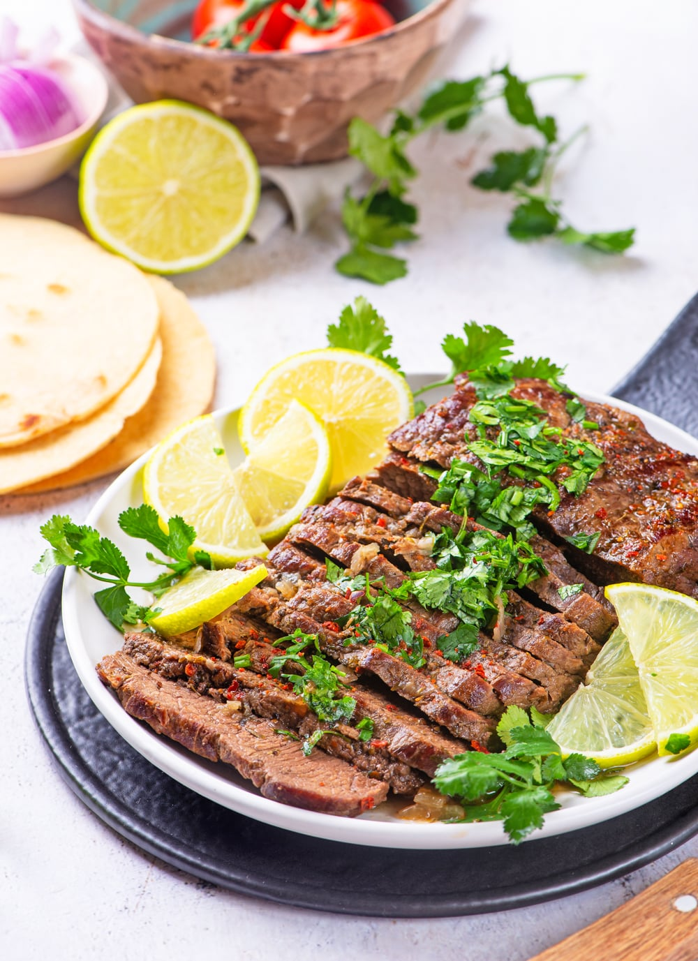 Cooked Flank steak cut up on a plate, and covered in chimichurri sauce.