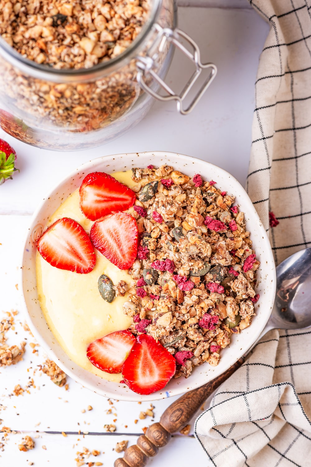 Granola, yogurt, and strawberries in a white bowl with a jar of granola next to it.