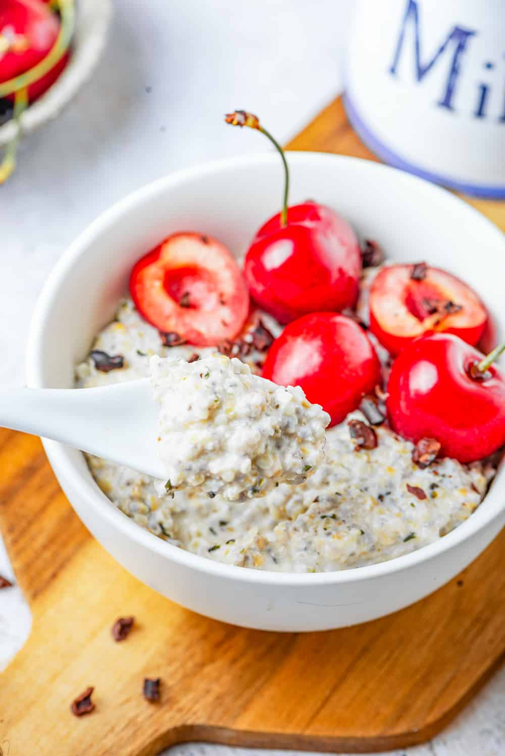 Oatmeal in a bowl with a white spoon taking some out.