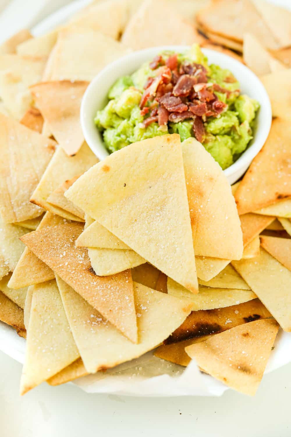 The side of a white platter that's full of tortilla chips and guacamole