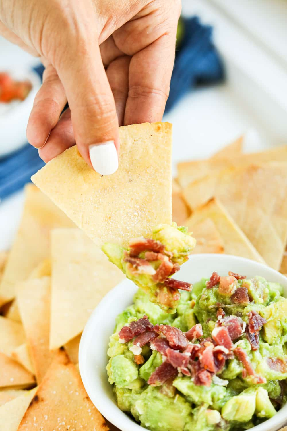 A tortilla chip scooping guacamole out of a bowl.