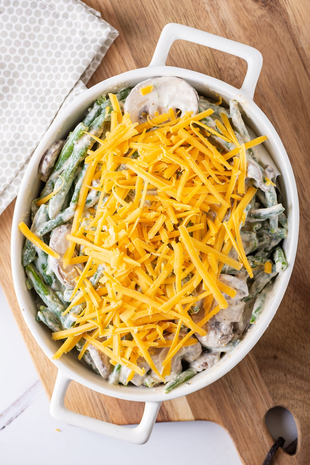 Green beans and mushrooms covered in a white sauce and topped with cheese in a white casserole dish.