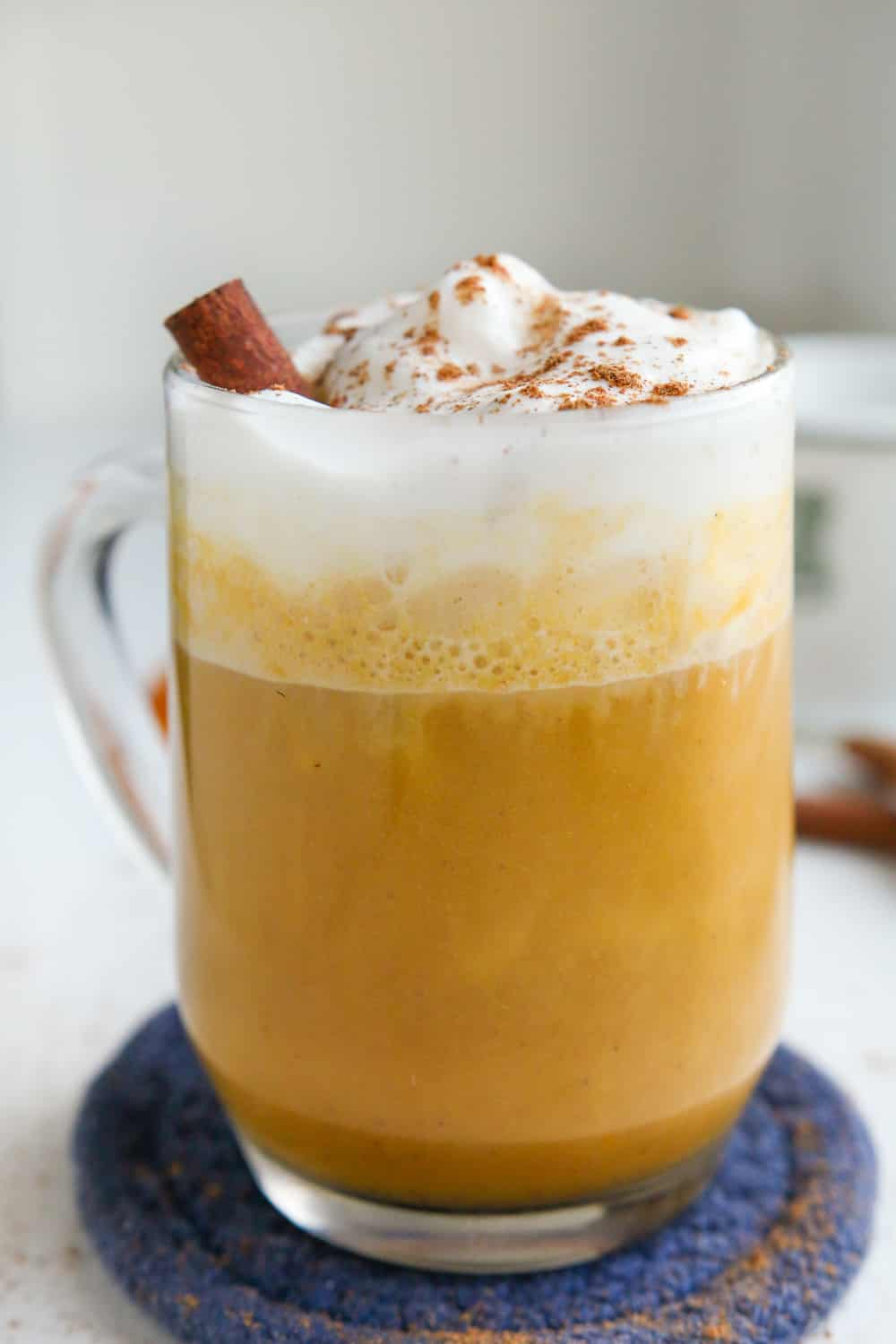 A pumpkin spice latte in a clear glass cup, and it's topped with whipped cream, a cinnamon stick, and spices.
