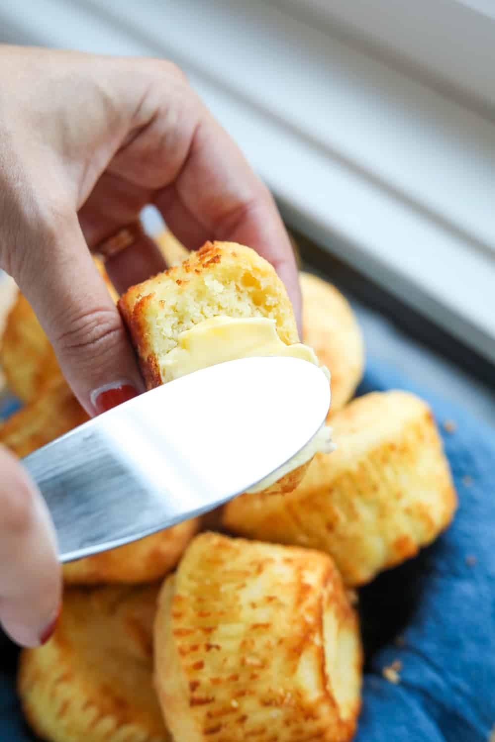 A hand holding a biscuit with a bite taken out of it and the other hand is spreading butter on it with a butter knife.