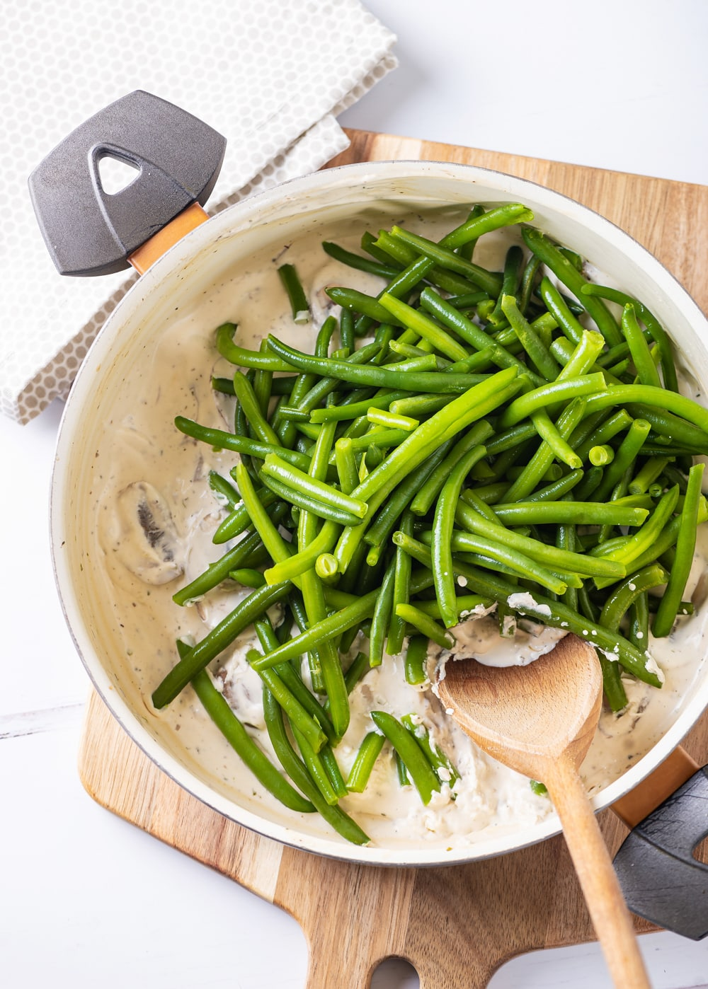 Green beans on top of mushrooms and a white sauce in a pot on top of a cutting board.