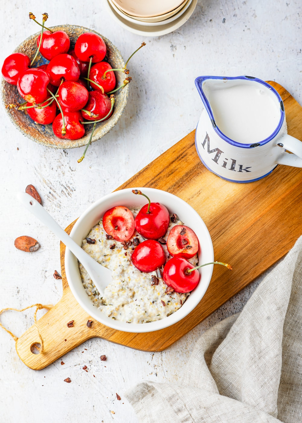 Oatmeal in a white bowl on a cutting board surrounded by a napkin, a small bowl of cherries, and a cup of milk.