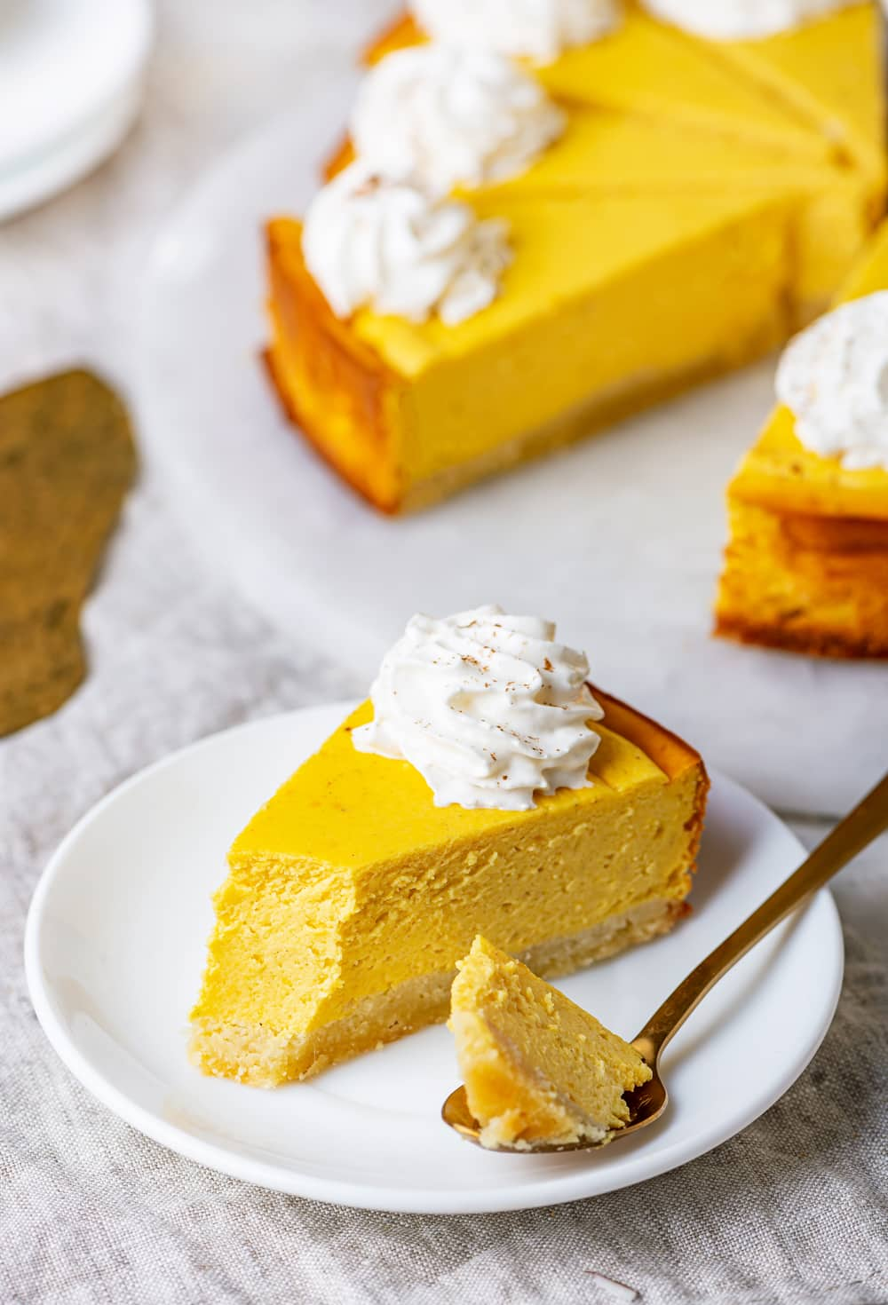 A slice of pumpkin cheesecake on a white plate with the rest of the slices behind it.