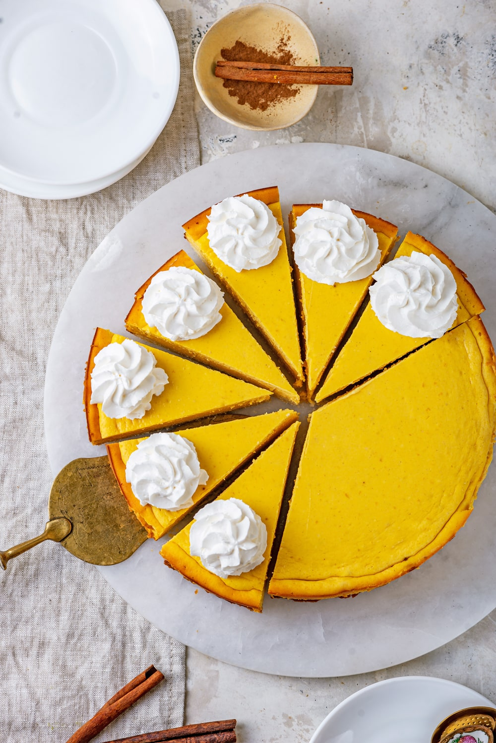 Pumpkin cheesecake cut into slices with a gold serving utensil under one of the slices.