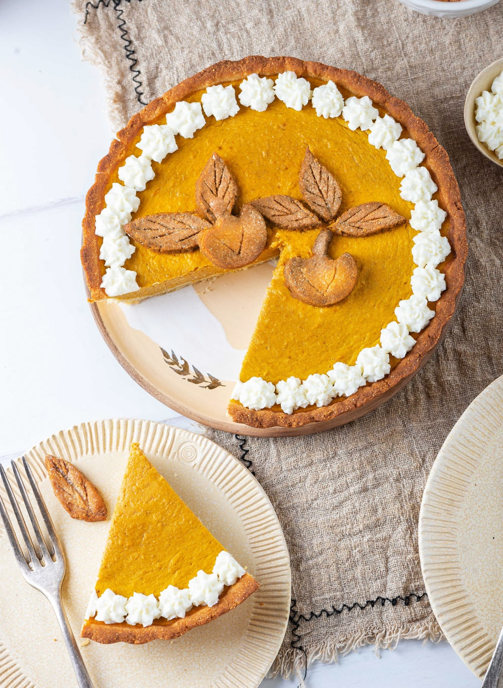 A slice of pumpkin pie on a plate set next to the entire pie.