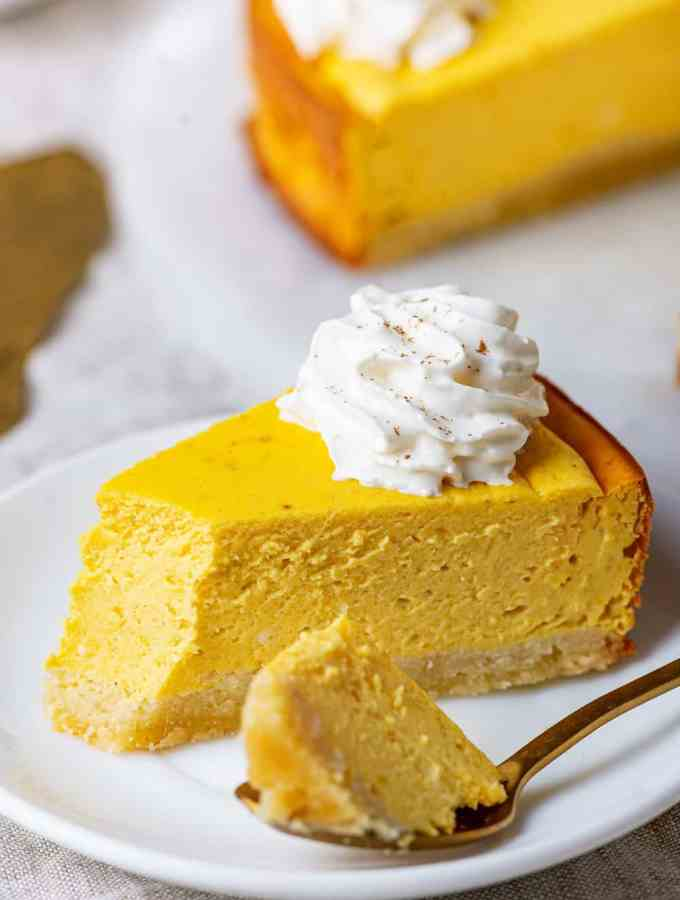 A slice of pumpkin cheesecake on a plate with a spoon holding a piece of it.