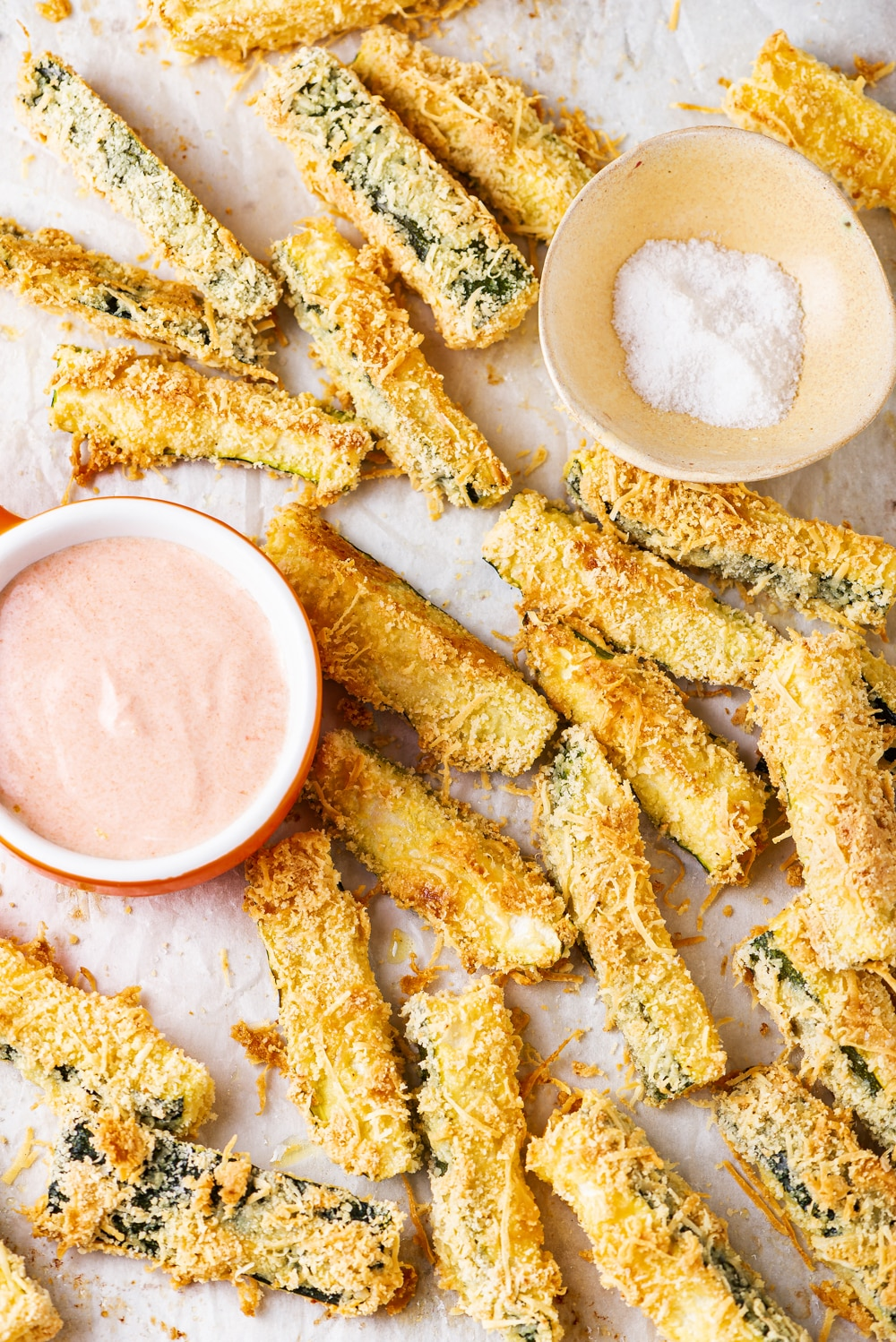 Zucchini fries on a tray with two small cups of dipping sauces.