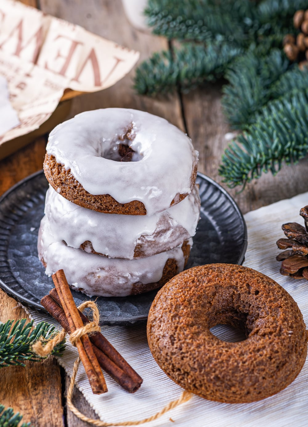 A stack of three glazed gingerbread donuts on a plate. An unglazed gingerbread donut is set to the right in front of the plate with a bundle of cinnamon to the left of the plate.