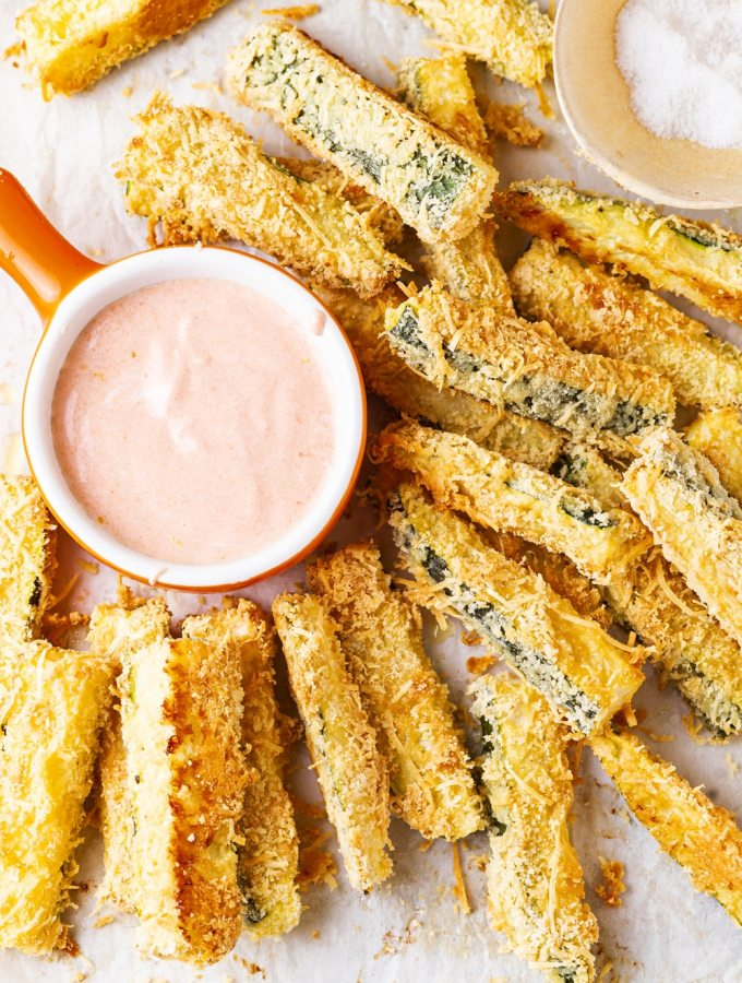 Breaded zucchini slices next to a cup of dipping sauce.