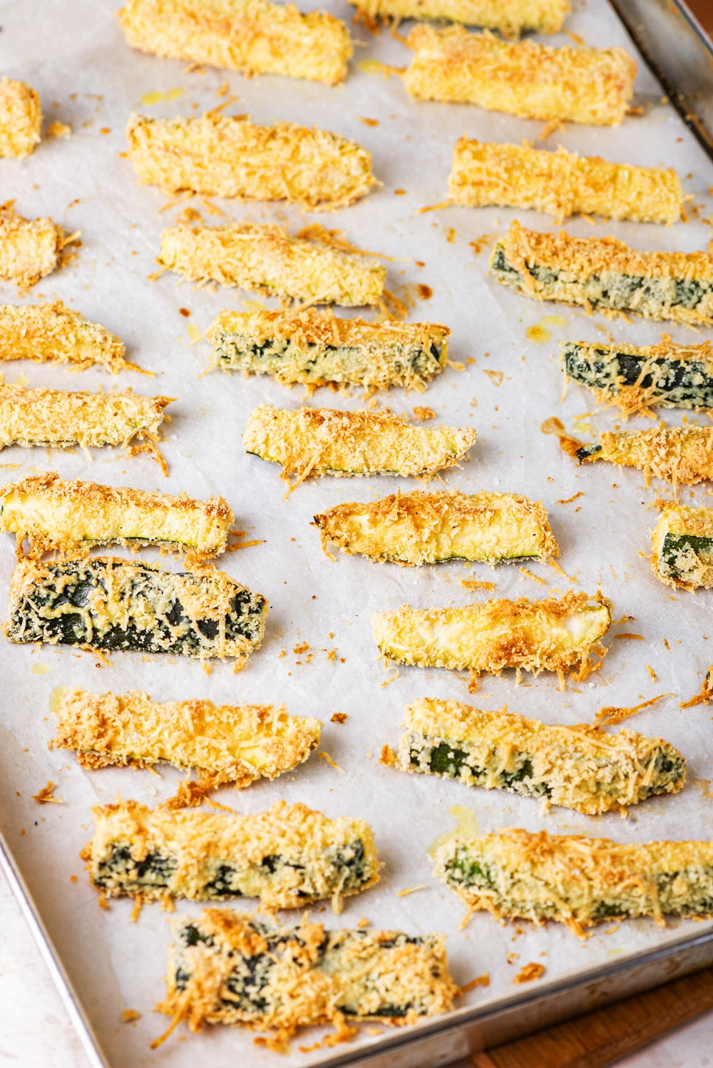 Slices of breaded and cooked zucchini on a baking sheet lined with parchment paper.