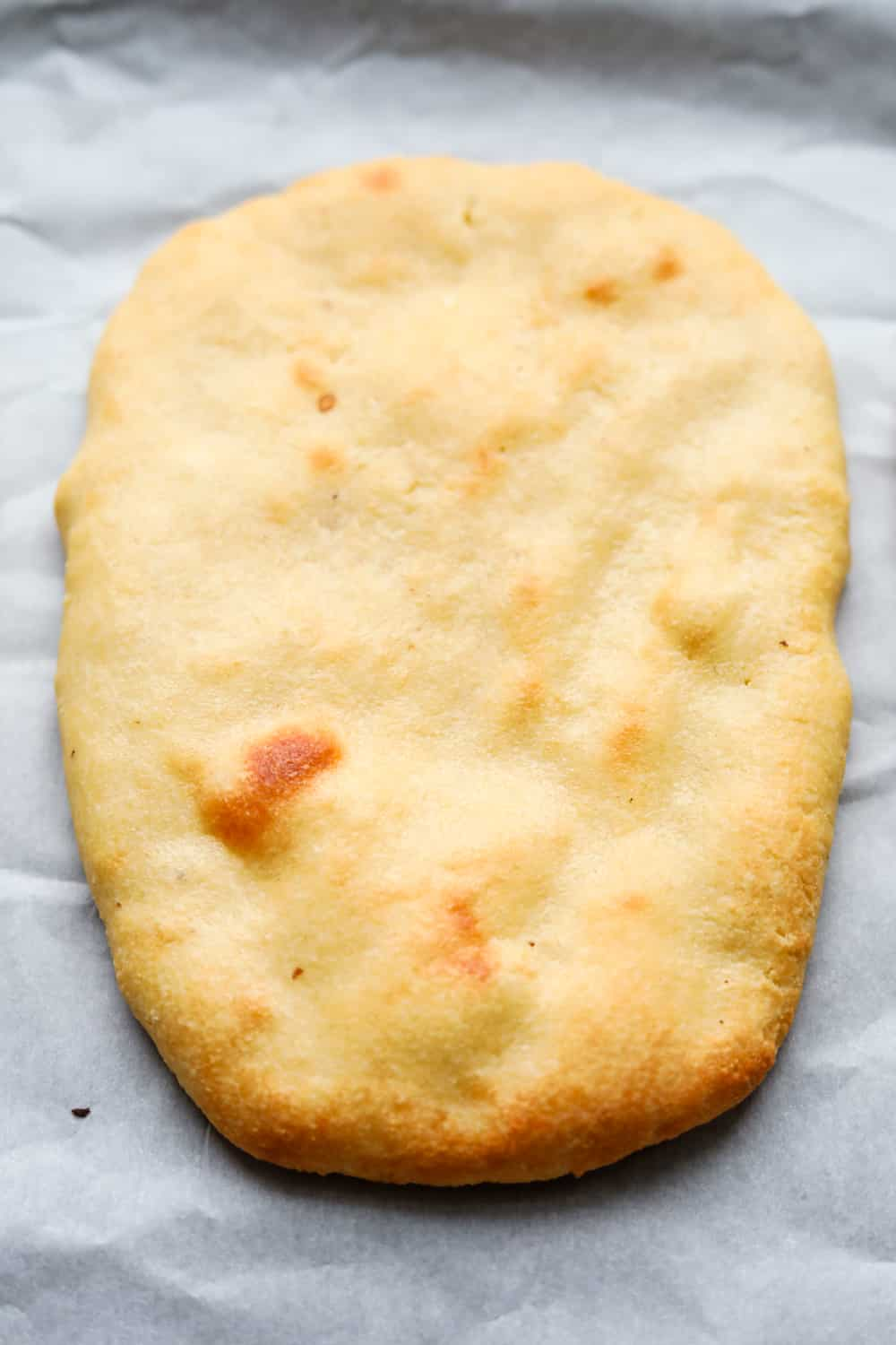 A plain naan bread on a white sheet of parchment paper.