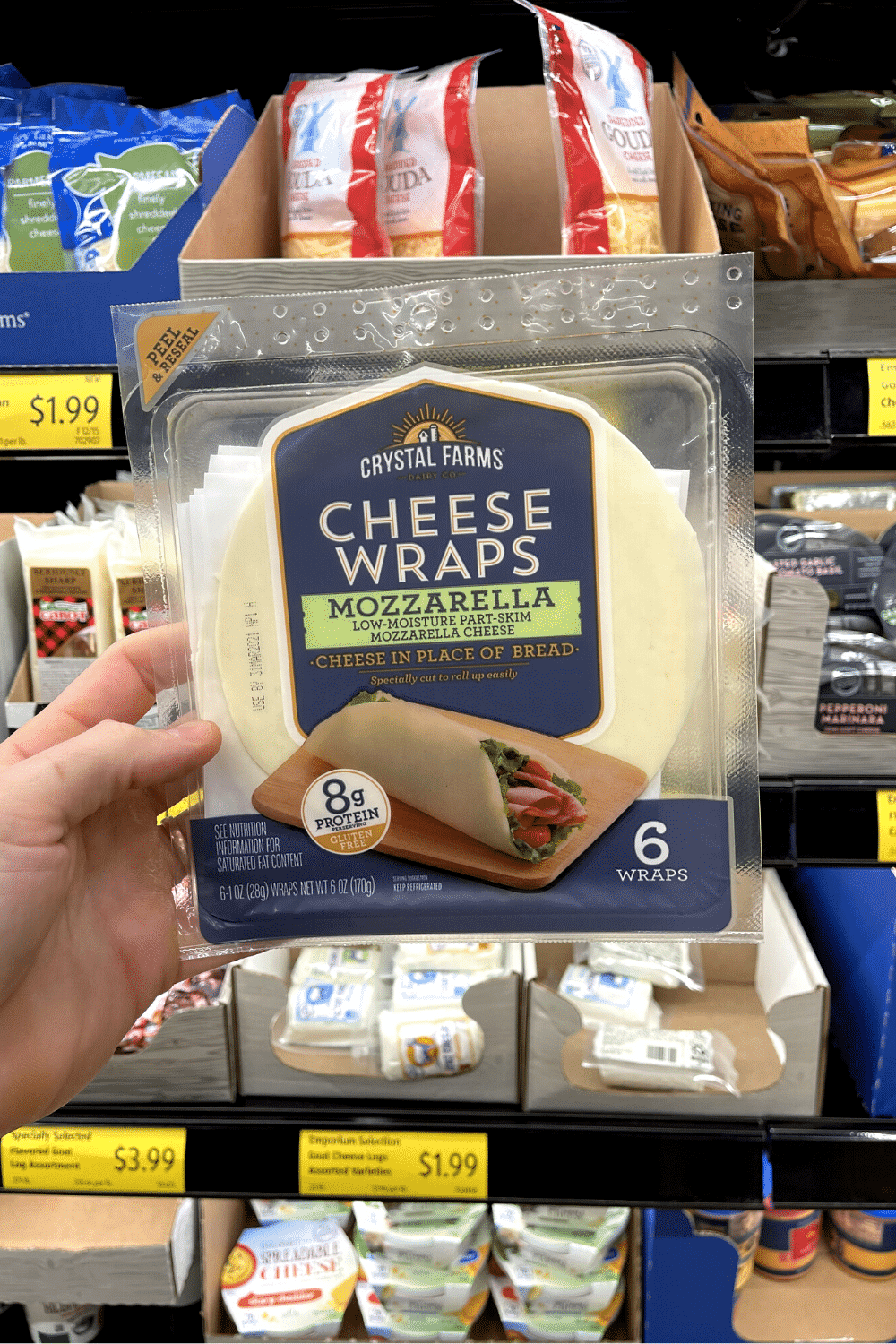 A hand holding a package of mozzarella cheese wraps.