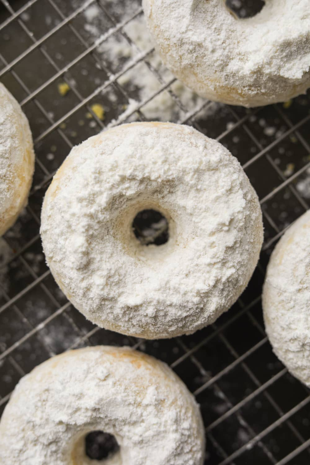 Powdered sugar donuts on a wire rack.