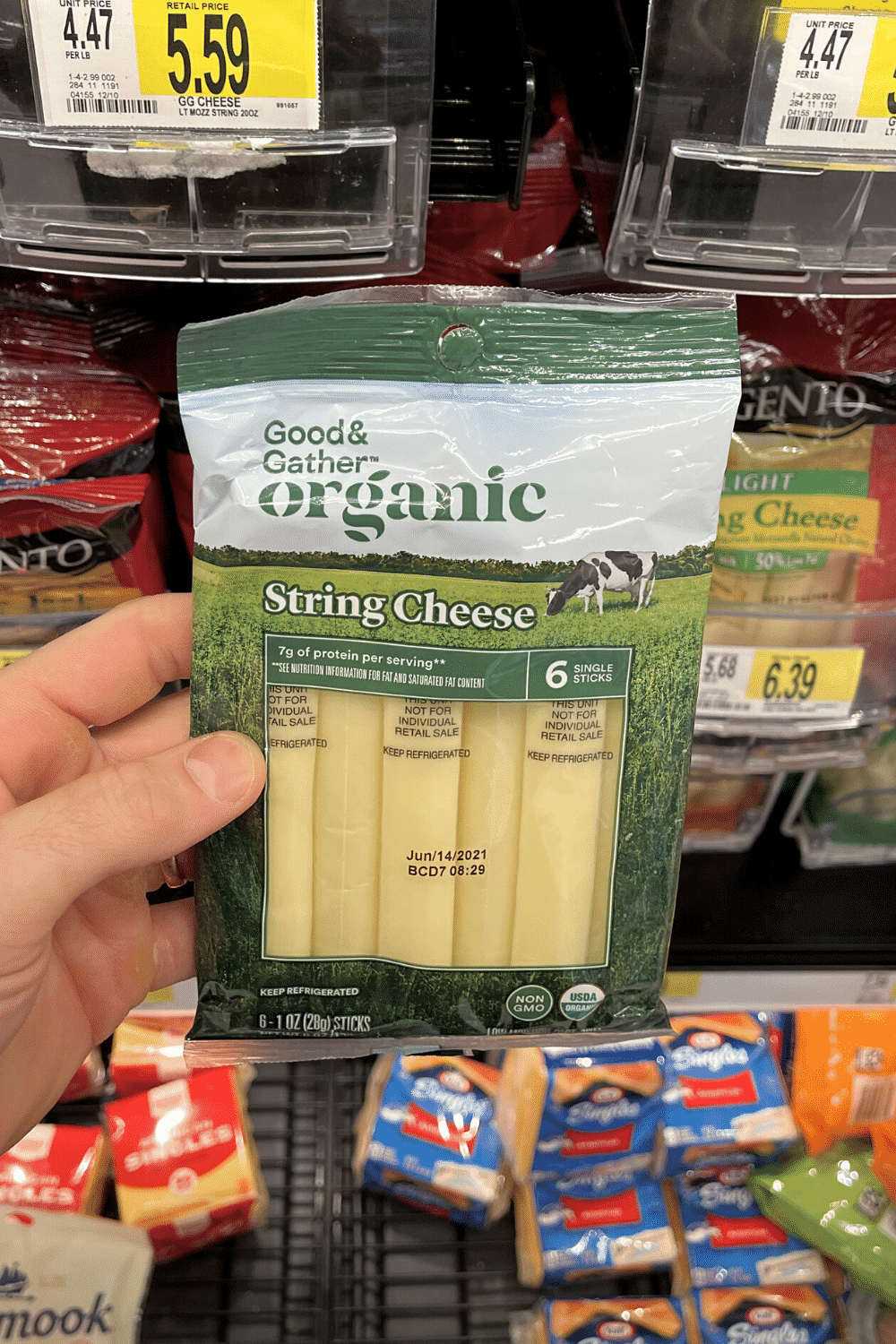 A hand holding a package of string cheese sticks.