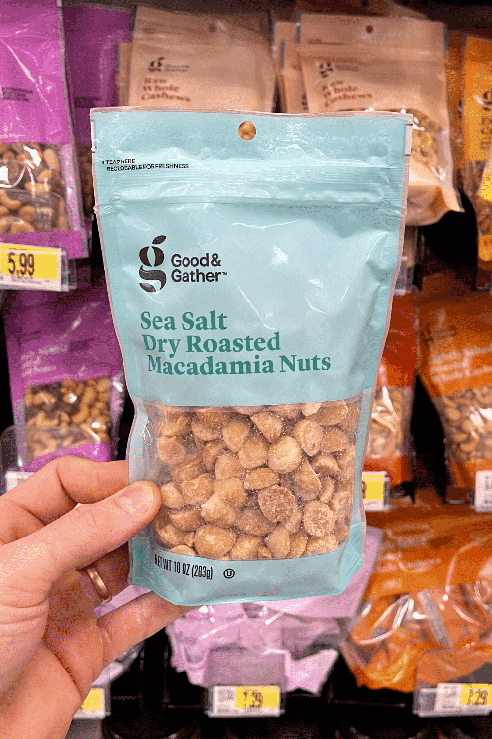 A hand holding a bag of dry roasted macadamia nuts holding a container of French onion dip.