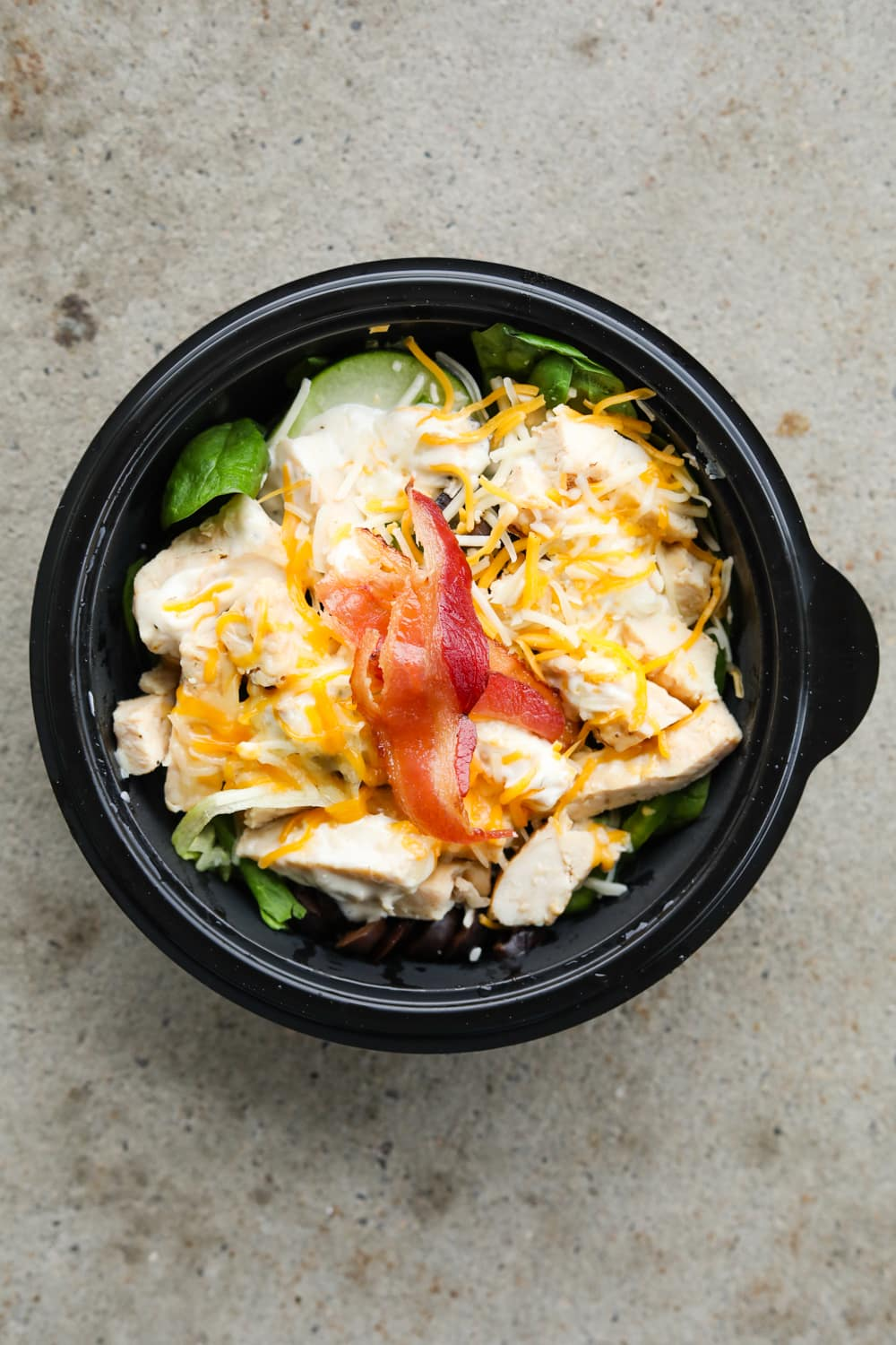 A black bowl filled with green vegetables, chopped chicken, ranch dressing, shredded cheese, and sliced bacon.