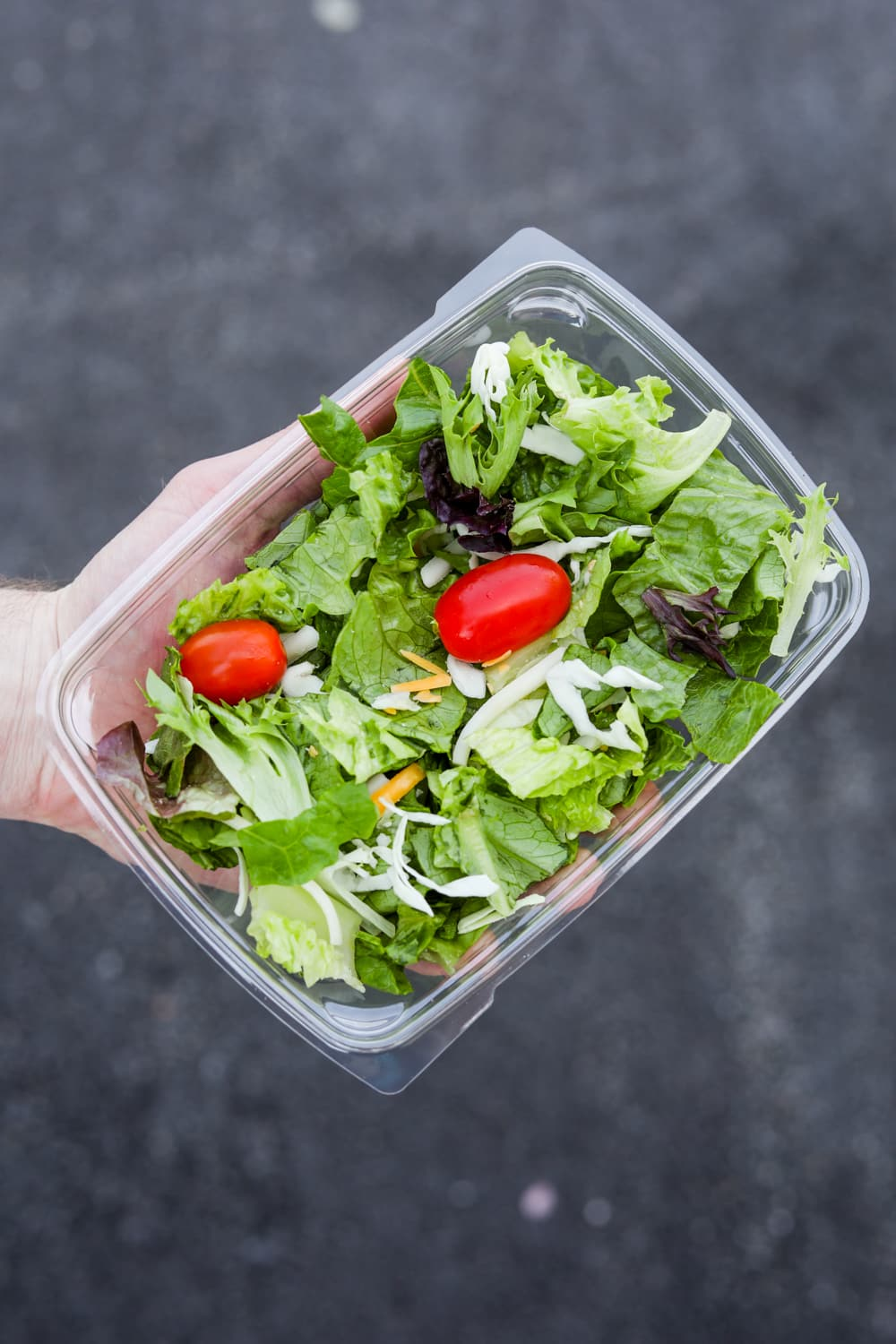A hand holding a container of side salad from Chick-fil-A.