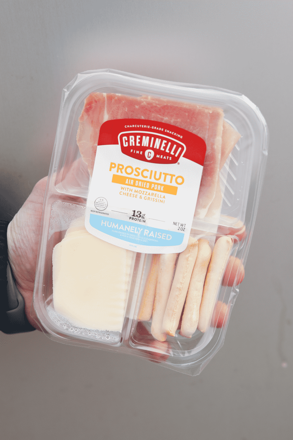 A hand holding a container of prosciutto, cheese and grissini.