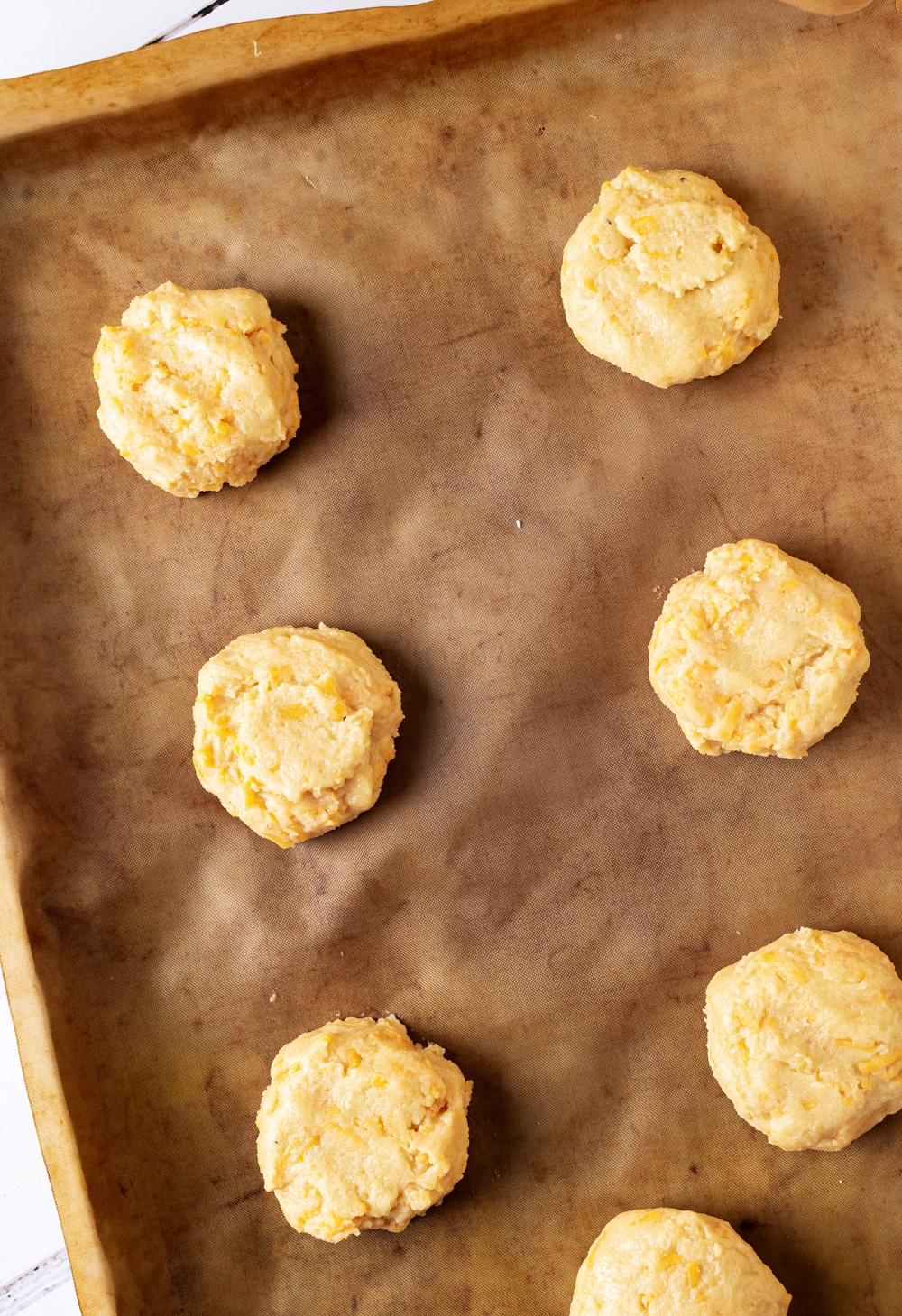 A piece of parchment paper on a baking sheet with seven keto cheddar biscuits on it.