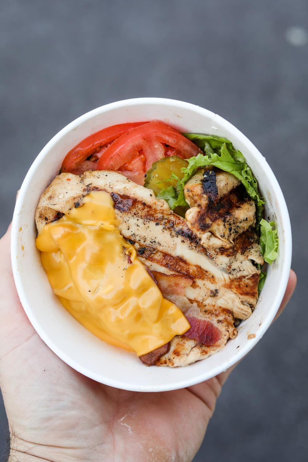 A hand holding a cup filled with a piece of grilled chicken, bacon, a slice of American cheese, lettuce, pickles, and tomato.