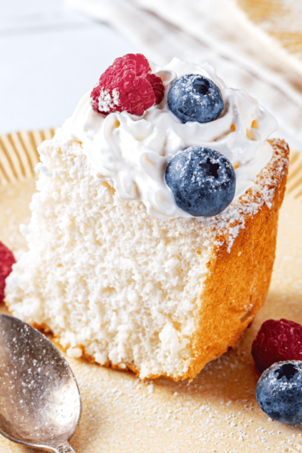 A piece of angel food cake on a plate. The piece of angel food cake has whipped cream and two blueberries and one raspberry on top.