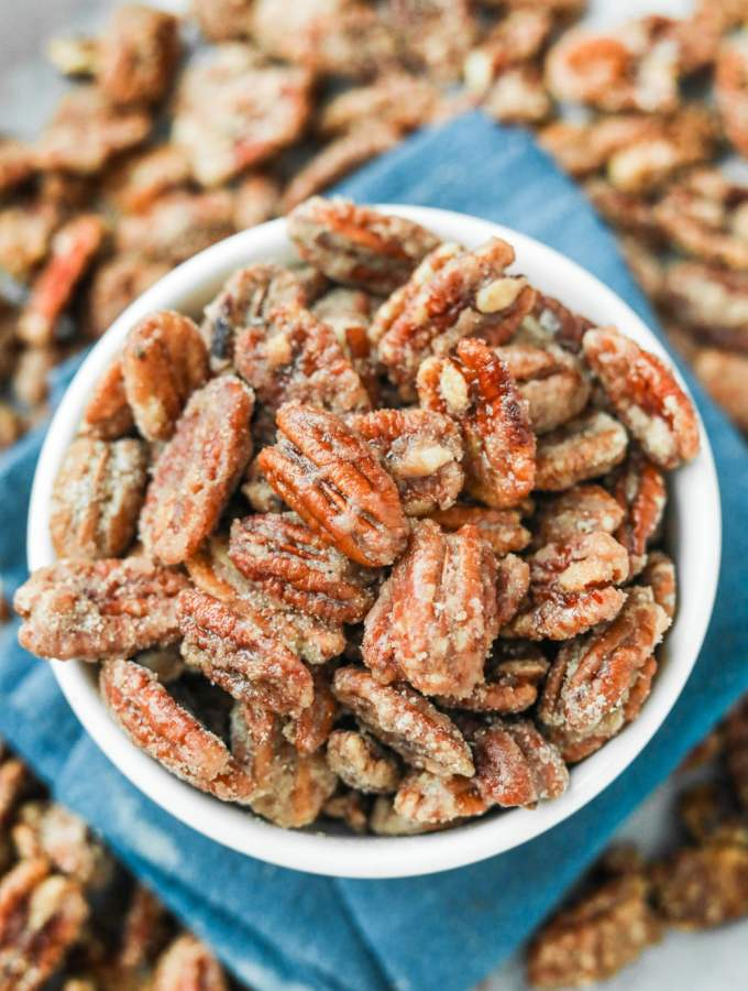 A white bowl filled with candied pecans. The bowl is set on a blue napkin.