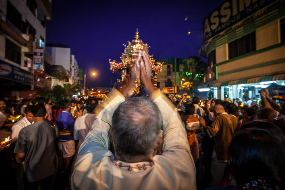 A devotee prays to the god Murugan and his silver chariot.