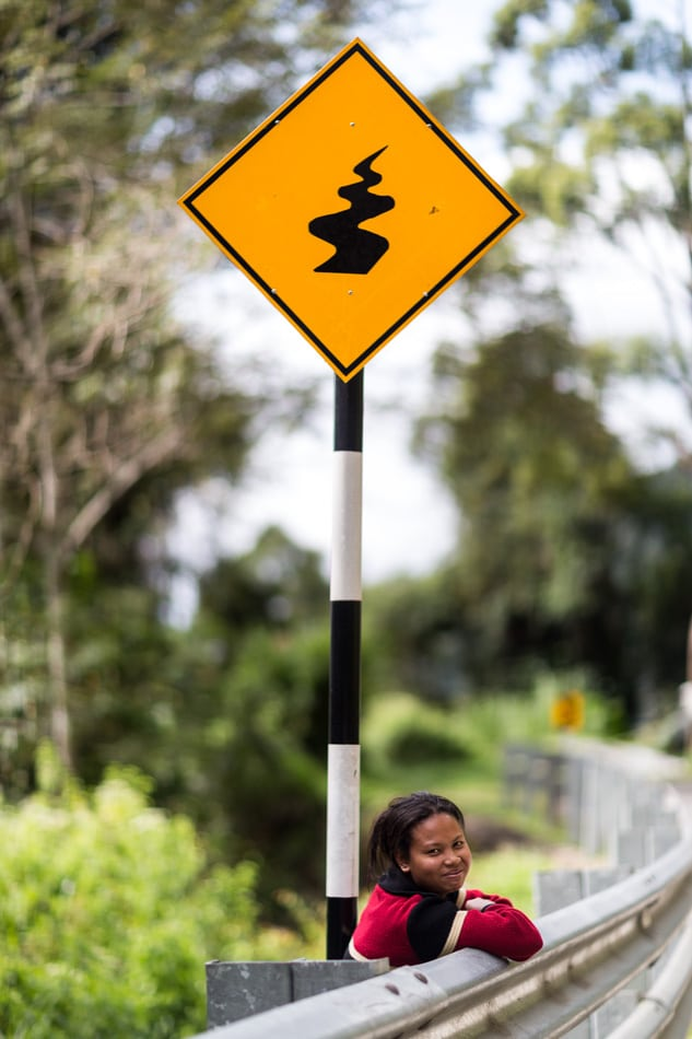 Orang Asli are the original people of Malaysia. Here a young Orang Asli woman waits under a curve warning sign.
