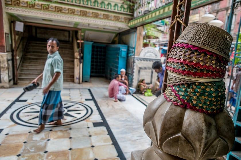 A man walks past straw prayer caps on his way into the Nakhoda Masjid.