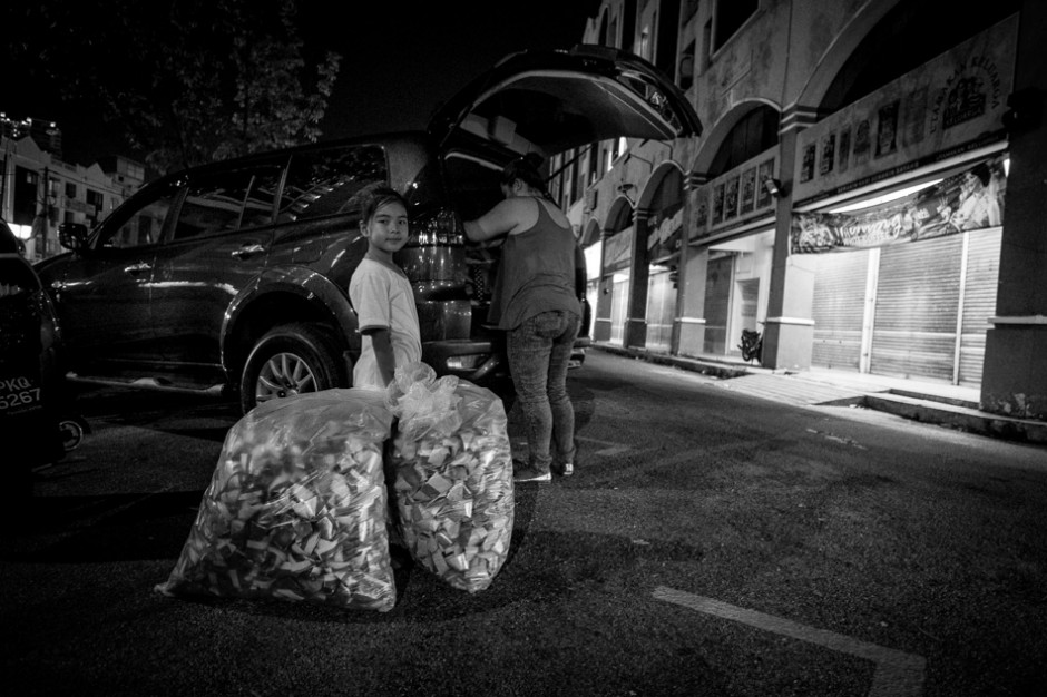"""Elsa passes Kai Xin bags of paper money called """"Hell notes"""". f/2.8, 1/12 sec, at 14mm, 3200 ISO, on a X-Pro1"""