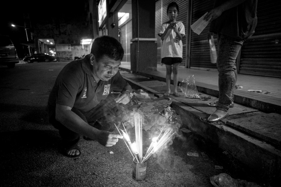 Kai Xin watches as her father put the joss sticks in with the other offerings and prepares to light the money.f/2.8, 1/25 sec, at 14mm, 3200 ISO, on a X-Pro1