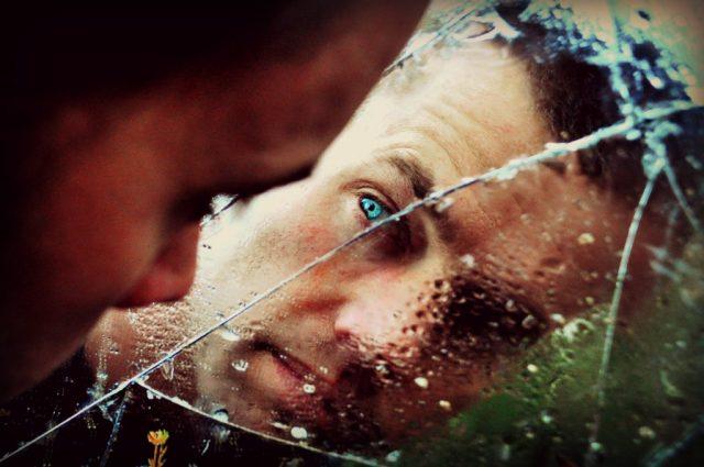 Depressed Man Looking Into Broken Mirror