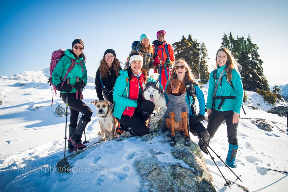 A group of women hiking in snow all geared up for winter
