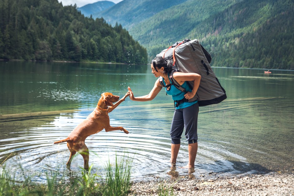 Viszla and woman high five in lake with Oru Kayak backpack