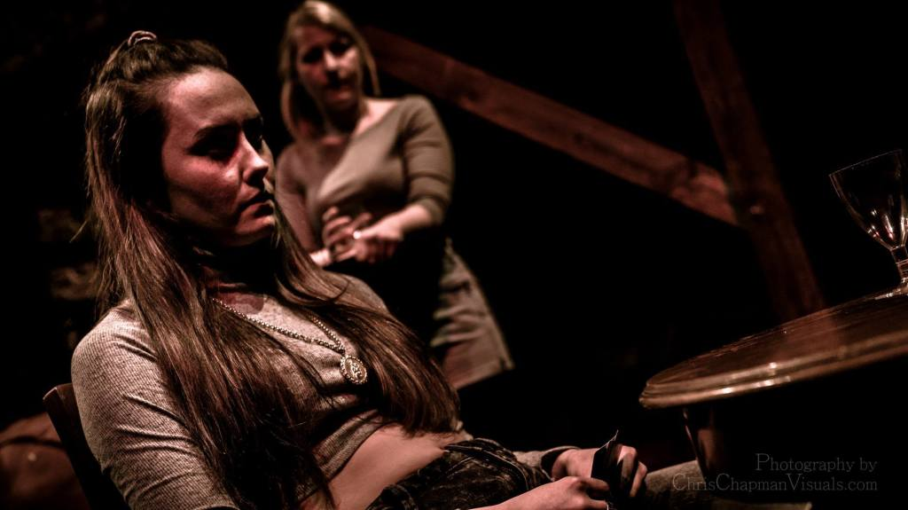 Our female Hamlet sits at a table waiting for the final scene