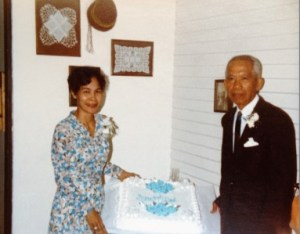 My parents show off their cake at their 25th wedding anniversary, May 1982.