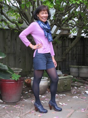 Welcome spring in navy shorts, pastel sweater, navy hose, and Frye covered-toe sandals.