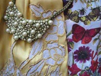 Enmeshed pearls from Urbanity (Berkeley, CA), linen appliques on maize-colored silk skirt from Personal Pizazz (Berkeley, CA), and colorful butterflies and flowers on a flowing blouse.