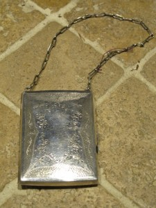 The etched cover of an antiqued compact purse.